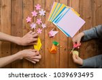 Small photo of Parent and child hand playing with origami