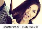woman combing her healthy hair... | Shutterstock . vector #1039758949