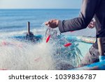 fisherman on boat with net in...