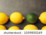 one lime among lemons on gray...   Shutterstock . vector #1039850269