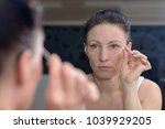 woman plucking her eyebrows... | Shutterstock . vector #1039929205