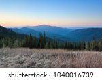 Stock photo panorama with mountains the lawn with dried grass magic forest sunrise spring landscape 1040016739