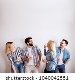 Stock photo group of young handsome colleague people standing against the wall having fun and drinking coffee 1040042551