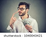 Small photo of Financial fraud concept. Liar business man with dollar cash