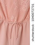 Small photo of Details of coral pink romper close up.