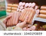 woman chooses sausages in a... | Shutterstock . vector #1040193859