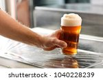 man holding a fresh glass of... | Shutterstock . vector #1040228239