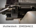 Small photo of Partial of the retro vintage typewriter. Close-up of the metallic carriage return lever, taking it to returns begin a new line.