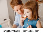 daughter is eating cupcakes... | Shutterstock . vector #1040333404