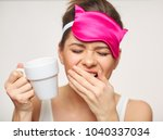 yawning woman holing coffee cup.... | Shutterstock . vector #1040337034