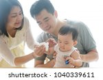mother wipes baby hand with... | Shutterstock . vector #1040339611