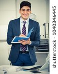 Small photo of Young businessman is signing agreement papers of financial nature at office.