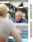 Elderly man studying among young college students in library and talking with girl - stock photo