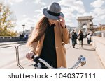 Stock photo serious woman in trendy beige coat driving around town in autumn morning outdoor portrait of shy 1040377111