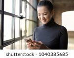 smiling woman checking her phone | Shutterstock . vector #1040385685
