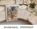 Coat of arms on the gate of Latin patriarchy buildings in Jerusalem - stock photo