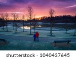 Small photo of Admiration - a low height aerial view from a drone of father and son admiring the sunrise over the trees and lake at the park in Beavercreek, Ohio.