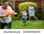 family are having a water fight ... | Shutterstock . vector #1040492044
