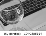 bitcoin in a glass on laptop... | Shutterstock . vector #1040505919
