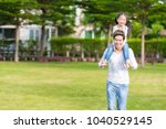 cute asian girl on neck dad big ... | Shutterstock . vector #1040529145