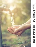 water from tap to woman hand in ... | Shutterstock . vector #1040595499