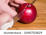 hand cuts a red apple with a... | Shutterstock . vector #1040703829