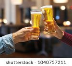 beer glasses raised in a toast. ... | Shutterstock . vector #1040757211