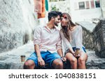 Stock photo romantic tourist couple sitting on stairs and drinking coffee 1040838151