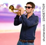 Small photo of Young Man Holding Trumpet, Outdoor