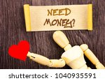 Small photo of Text sign showing Need Money Question. Conceptual photo Economic Finance Crisis, Cash Loan Needed written Sticky Note Love Heart Holding By Sculpture the wooden background.