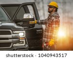 Energy Sector Worker in the Field. Electrical Infrastructure Construction Technician and His Company Truck. High Voltage Lines Maintenance. - stock photo