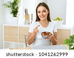 smiling woman eating nuts in... | Shutterstock . vector #1041262999