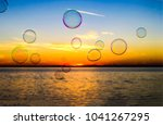 air bubbles on sunset water... | Shutterstock . vector #1041267295