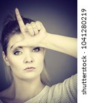 Small photo of Woman showing mean sign, lame or loser gesture with L fingers on forehead, grey background.