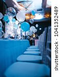 Small photo of Blue white and silver balloons hang over blue dinner table in the dinner hall