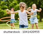 children playing with hoops in... | Shutterstock . vector #1041420955