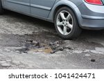 big pothole caused by freezing... | Shutterstock . vector #1041424471