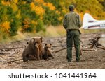 Small photo of Park ranger trying to scare away mama-bear with her cubs.