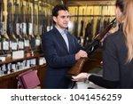 confident salesman in gun shop... | Shutterstock . vector #1041456259