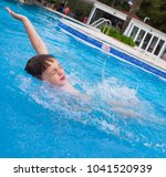 Small photo of Little boy having fun playing in the pool, jumping and water splashing during summer vacation on the seaside. Angled for impact. Angled for impact.