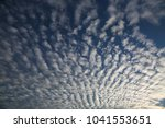 Small photo of Texture of altocumulus shape clouds at sky on sunset.