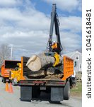 Small photo of Somerset, Massachusetts, USA - March 31, 2015: Section of thick trunk of downed Norway Spruce tree being placed in truck for removal