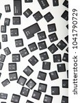 Small photo of Loose alphanumeric covers for the keys on a laptop computer keyboard scattered randomly on a white surface viewed high angle with foreground copy space