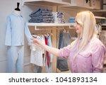 beautiful young woman near rack ... | Shutterstock . vector #1041893134