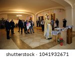Small photo of Christening for baby in a rural church. Priest reading Bible and next of kin, and a woman standing with a baby on hands. January 7, 2018. Bucha village, Ukraine