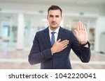 Small photo of Honest trustworthy real estate agent making oath swear vow gesture on new apartment building lobby background