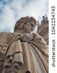 Small photo of Fragment of the monument to Dante Alighieri. The statue standing next to the Basilica of Santa Croce in Florence Italy. Against a basilica and vivid background blue sky with clouds.