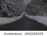 a snow covered country road in... | Shutterstock . vector #1042265425