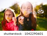 girls play with soap bubbles. | Shutterstock . vector #1042290601