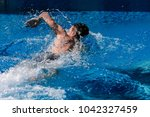 a man beautifully swims in the... | Shutterstock . vector #1042327459